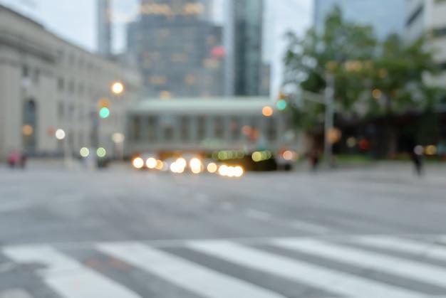 トラフィックライトカラフルなボケと建物が付いている都市のぼやけている横断歩道