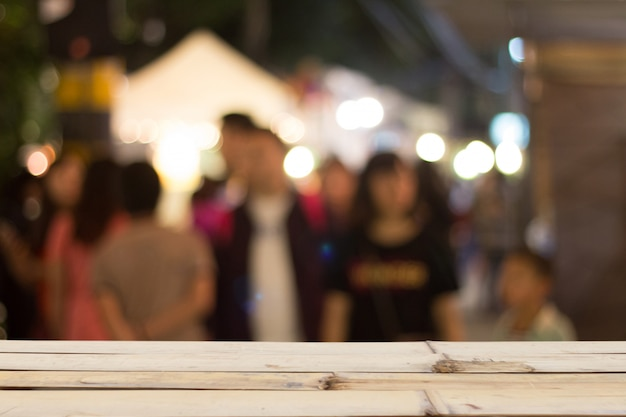 Blurred people on night street and wooden tabletop on font
