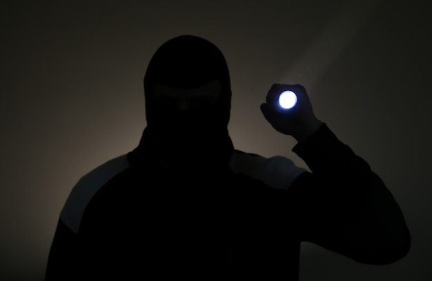 Blurred photo. burglar in dark clothes holding the flashlight. dangerous robber in mask with a torch. criminal man.