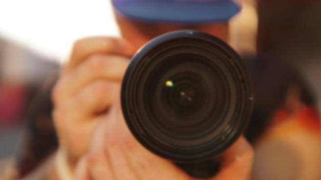写真レンズを持つ男のぼやけた写真のクローズアップ