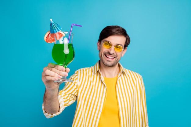 긍정적인 쾌활한 남자 관광객의 흐릿한 사진은 리조트의 오싹한 모습을 즐기고 파란색 배경에 격리된 흰색 옷을 입고 알코올 칵테일을 즐깁니다.