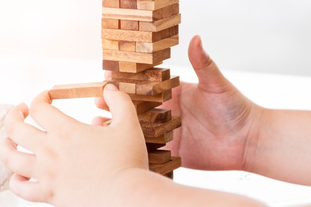 Blurred picture of boy's hands play wooden block toy
