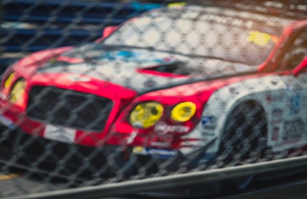 Blurred picture of fence mesh netting and car on racetrack. motorsport car racing on asphalt road. super racing car on street circuit. automotive industry concept.
