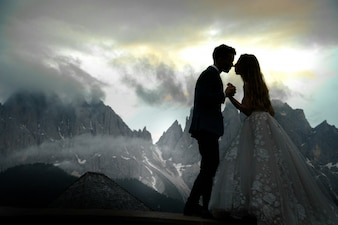 Blurred picture of kissing wedding couple standing before gorgeous mountain landscape