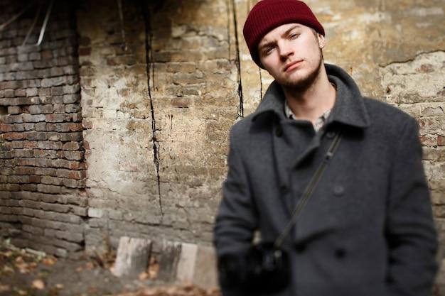 Размытое изображение человека в сером пальто, стоящем перед разрушенной стеной