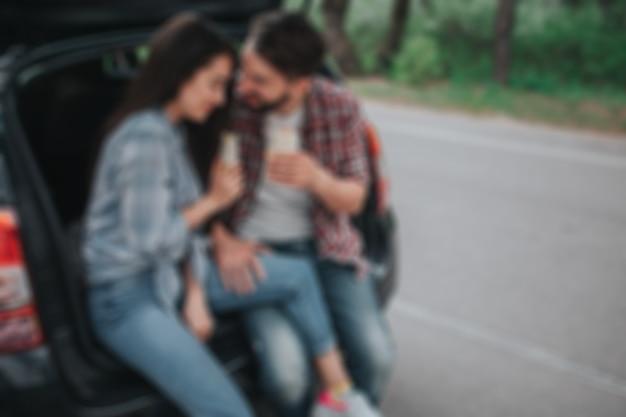 트렁크에 앉아서 손에 롤을 들고 있는 젊은 부부의 흐릿한 사진. 남자는 여자를 찾고 있습니다. 그녀는 그의 어깨에 기대고 있다. 그들은 행복해 보인다