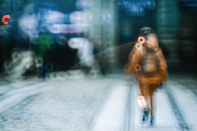 Immagine sfocata di persona che cammina lungo la strada