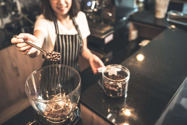 Blurred portrait of a barista asian woman scooping roasted coffee beans into a coffee grinder