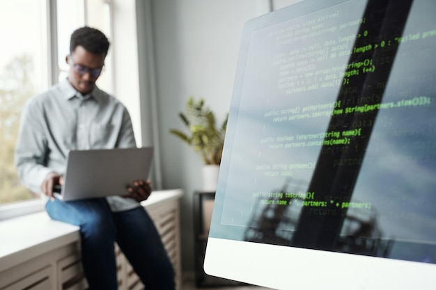 Размытый портрет молодого афроамериканца, использующего ноутбук, сидя у окна в офисе разработки программного обеспечения, экран кода на переднем плане, пространство для копирования