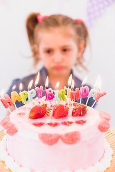 Blurred portrait of a sad girl standing behind strawberry birthday cake