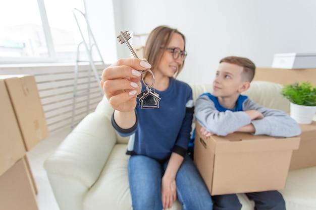 흐릿한 긍정적 인 엄마와 아들이 소파에 앉아 새 아파트의 열쇠를 보여주고 있습니다.