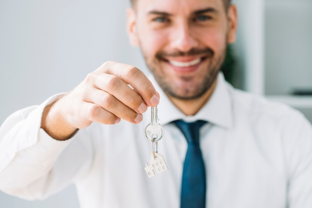 Blurred real estate agent holding key