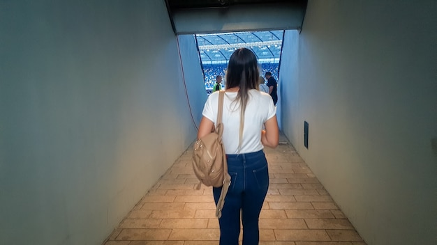 Blurred rear view image of young woman entering stadium through gate and walking on the tribunes