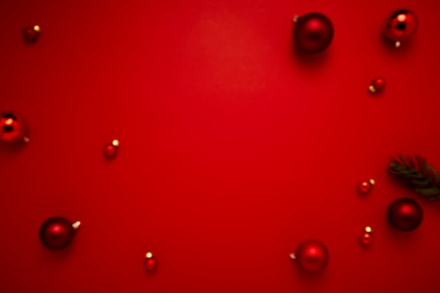 Blurred red christmas baubles decoration on paper red background with copy space for new year and merry christmas