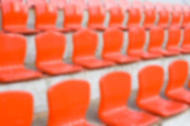 小さなスタジアムのぼやけた赤い空のプラスチックシート。水平方向のぼかしの背景