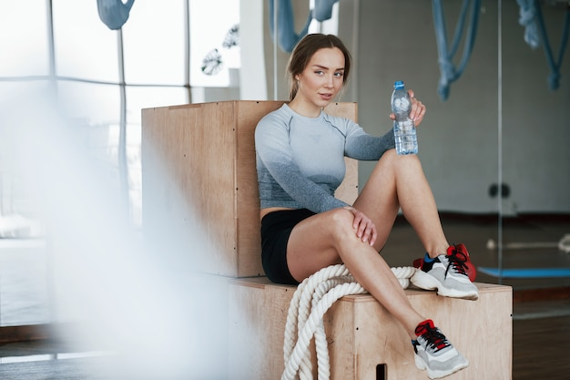 Blurred rope in front of camera. sportive young woman have fitness day in the gym at morning time