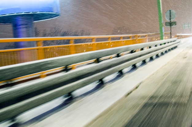 Blurred safety travel barrier construction in viaduct covered with snow