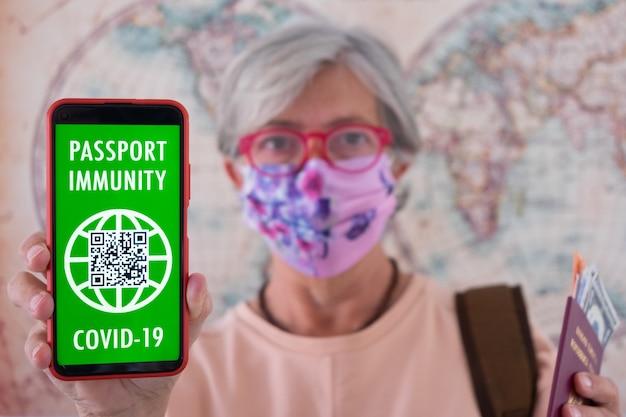 ぼやけた年配の女性は、ワクチン接種を受けた人々のためのグリーンパス携帯電話デジタル健康パスポートアプリを示しています