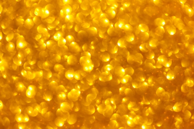 Blurred shiny golden background with sparkling lights.