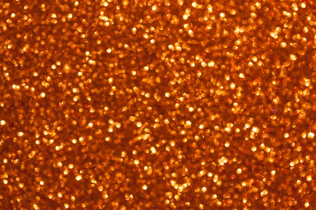 Blurred shiny golden background with sparkling lights