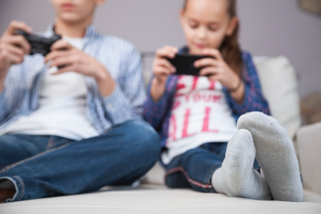 Blurred siblings playing video game and using smartphone