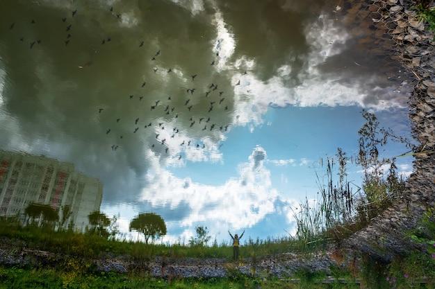 도시 공원에 있는 한 사람의 호수에 반사된 흐릿한 실루엣 추상 사진