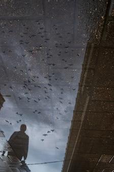 비오는 날 젖은 도시 보도에서 혼자 걷는 한 사람의 흐릿한 실루엣