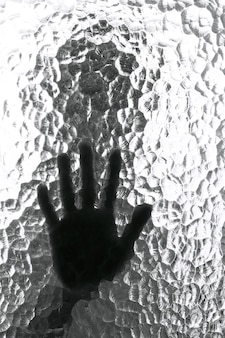 Blurred silhouette of a person and its hand behind a door with texture glass