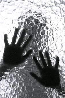 Blurred silhouette of a person and its hands behind the door with texture glass