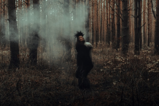 Blurred silhouette of a terrible witch with a skull in her hands performing a mystical occult satanic ritual in a dark gloomy forest