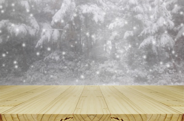 Blurred snowing in pine forest through glass window background with wood table.