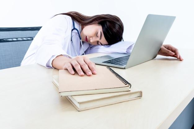 아시아의 매력적인 여성 의사의 흐릿한 부드러운 이미지는 그녀가 일에 지친 책상에 앉아 있었다