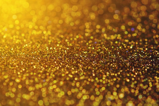 Blurred sparkling gold color glitter light as abstract festive background