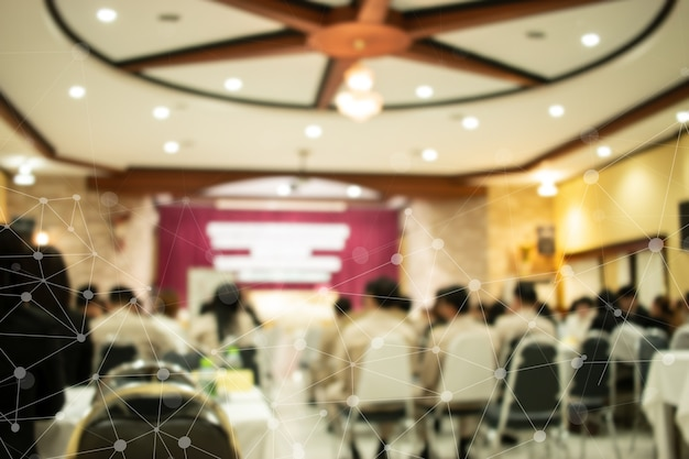 Blurred of speaker on stage iot network, rear view group audience listens speech lecturer in conference hall or seminar at hotel, business and education meeting concept