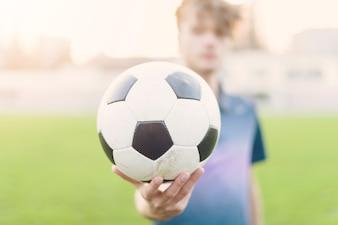 Размытый спортсмен показывает футбольный мяч