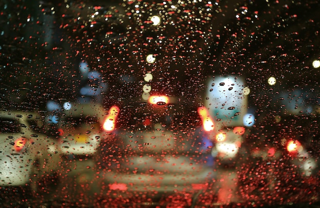 Blurred street lights and tail lamps seen through the raindrops on car windshield at night