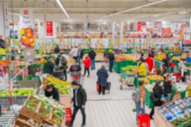 ぼやけたスーパーマーケット。小売店で商品を販売する。店内の買い物客の背景がぼやけている。