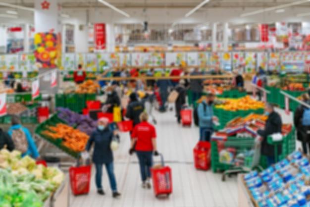 흐리게 슈퍼마켓. 소매점에서 상품 판매. 상점에서 쇼핑객의 배경을 흐리게.