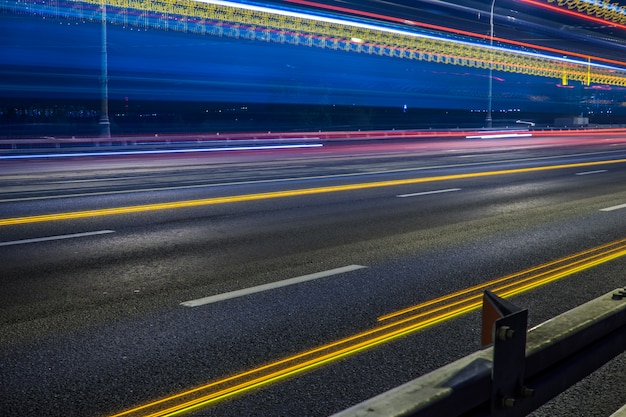 Blurred tail lights and traffic lights on road