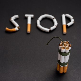 Blurred text stop made from cigarette with bundle of cigarette with wick above black background
