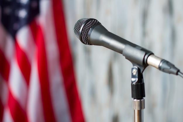 ぼやけた米国旗とマイク。バナー横のスタンドにマイク。全国が注目します。スピーカーを待っているトリビューン。
