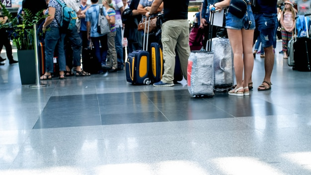 Blurred view of crowd of people with bags standing in queue in airport terminal.