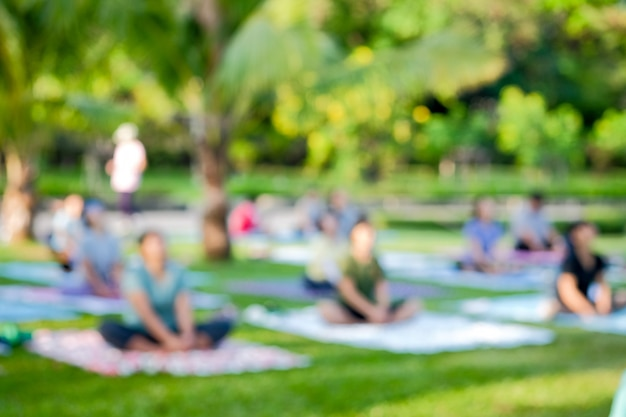 Blurred view a group of thai people was practice yoga exercise on public parks