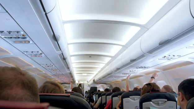Blurred view of long row of seat and ceiling in airplane.