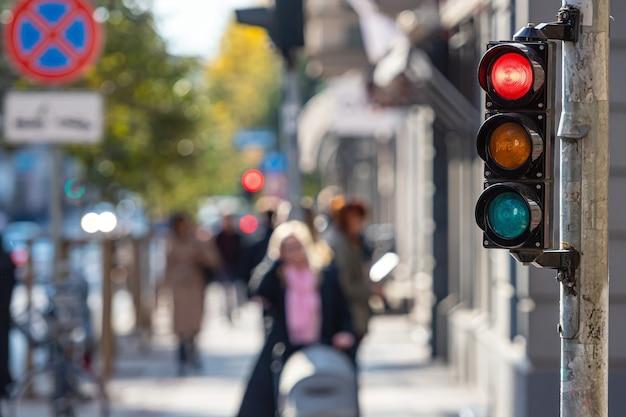 Размытый вид городской улицы с пешеходами и светофорами