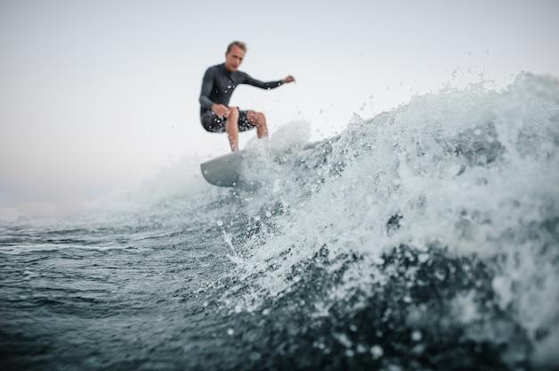 前景に焦点を当てて波を乗り降りしてぼやけたウェイクサーファー