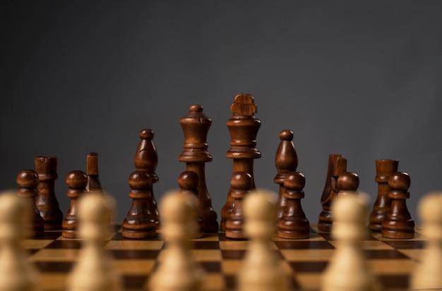 체스 판에 검은 체스 인물의 그룹에 대한 흐린 흰색 폰