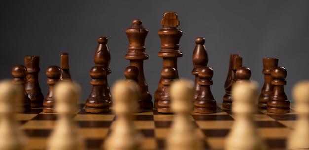 Размытые белые пешки против группы черных шахматных фигур на шахматной доске.