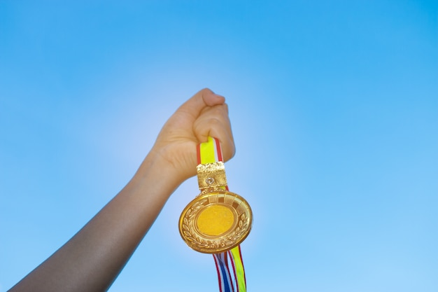 Blurred of woman hands raised and holding gold medals with thai ribbon against blue sky background to show success in sport or business, winners success award concept.