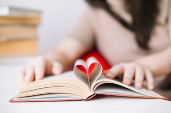 Blurred woman holding book with heart